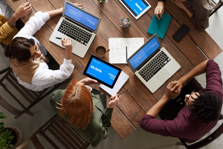 https://www.pexels.com/photo/top-view-photo-of-group-of-people-using-macbook-while-discussing-3182773/